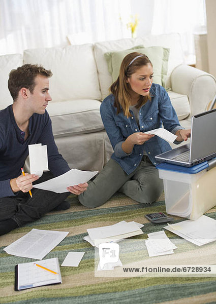 USA  New Jersey  Jersey City  Portrait of young couple doing paperwork at home