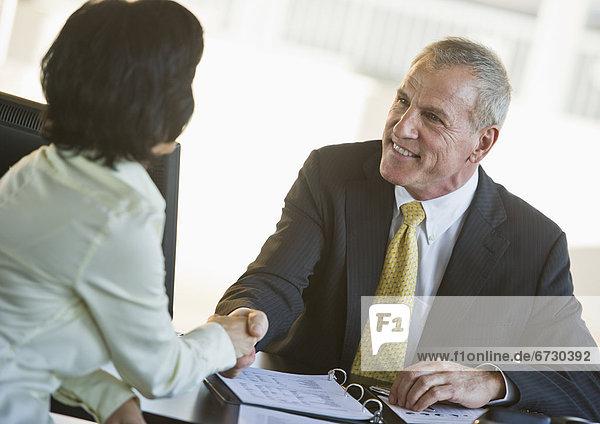 Geschäftsfrau und Händeschütteln Kaufmann