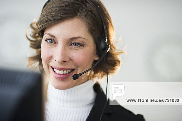 USA  New Jersey  Jersey City  of smiling woman with headset in customer service office