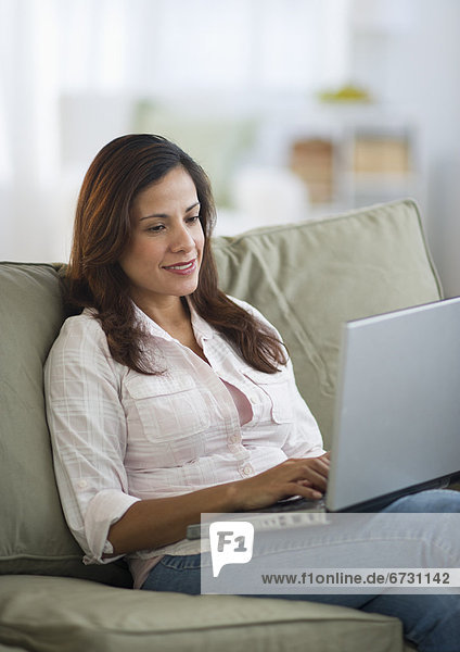 USA  New Jersey  Jersey City  woman sitting on sofa and using laptop