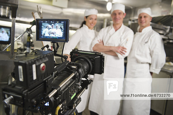 Three chefs posing in kitchen  camera in foreground