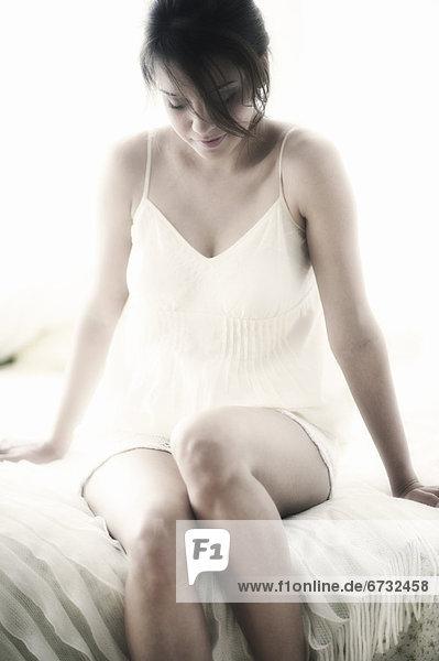 sitzend  Frau  Nachtkleidung  Bett  jung