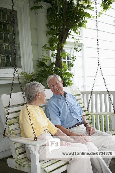 sitzend Senior Senioren schaukeln schaukelnd schaukelt schwingen schwingt schwingend Vordach Schaukel
