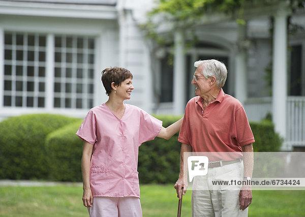 Senior Senioren Mann Assistent gehen Garten Sorge