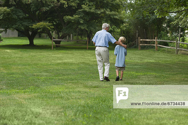 Grandfather and grandson (10-11) walking in park