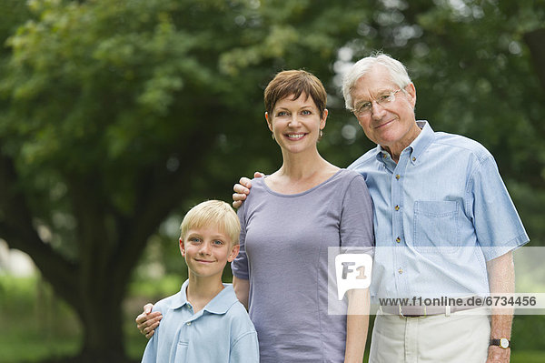 Three generation family standing in park