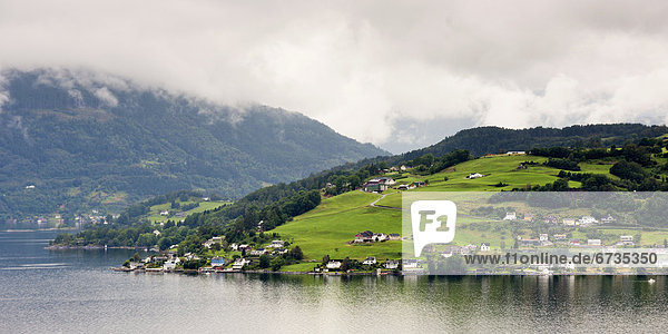 'Houses On A Hill Along The Water's Edge Of Hardangerfjord