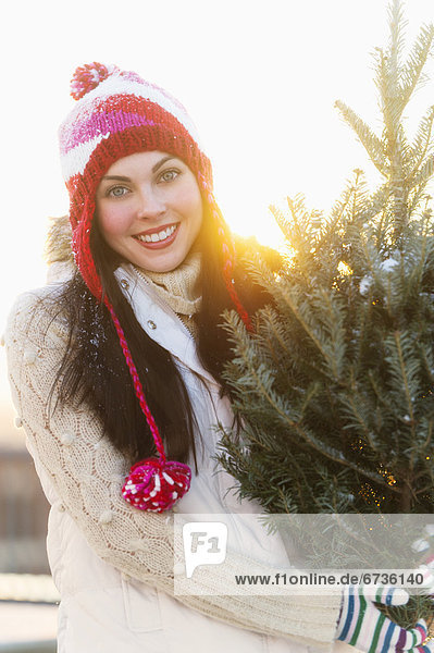 Portrait of young woman carrying Christms tree