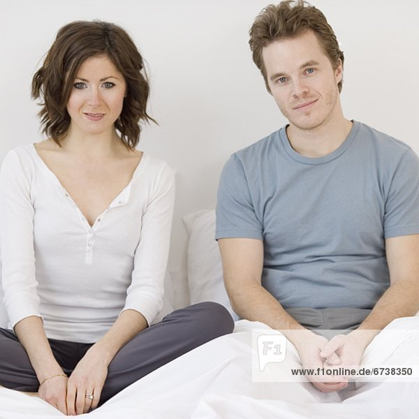 Paar im Bett sitzend