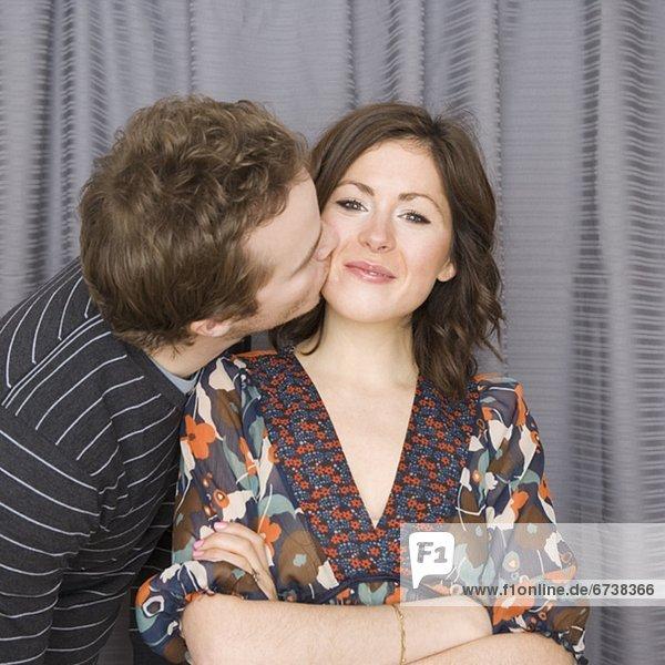 Mann küssen Freundin auf Wange