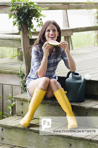 Frau  Stiefel  Wassermelone  Terrasse  Kleidung  essen  essend  isst  Gummi