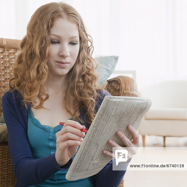Woman reading ads in paper
