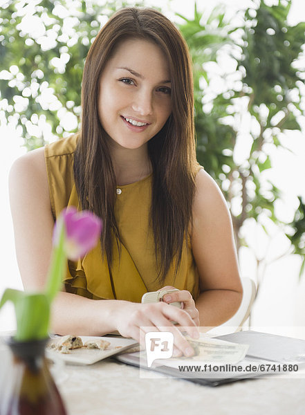 Außenaufnahme junge Frau junge Frauen Portrait lächeln Cafe bezahlen zahlen Rechnung freie Natur