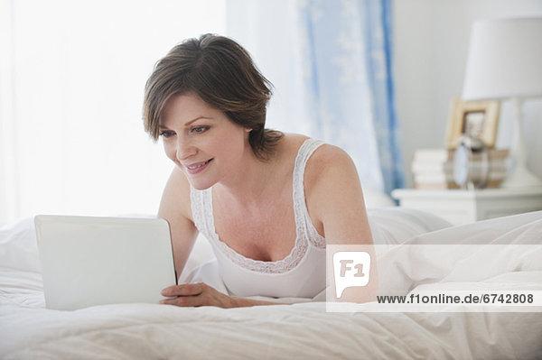 Frau benutzt Laptop im Bett