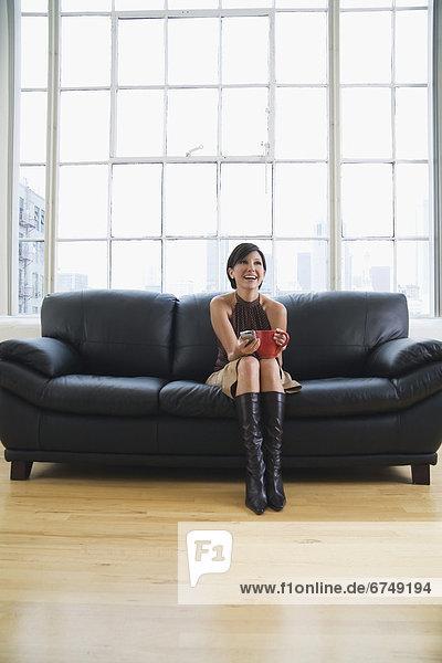 Frau  lachen  Becher  halten  Couch