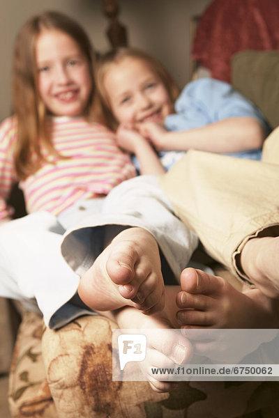 barfüßig  2  jung  lächeln  Couch  Mädchen