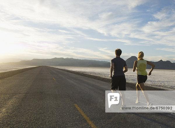 Couple running on road  Utah  United States