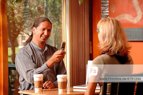 Couple having Coffee  Man Using Cellphone