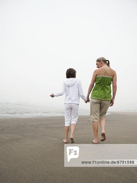 Mutter und Tochter halten Händchen und laufen am Strand