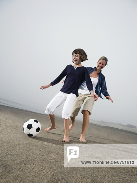 Mother and daughter kicking soccer ball on beach