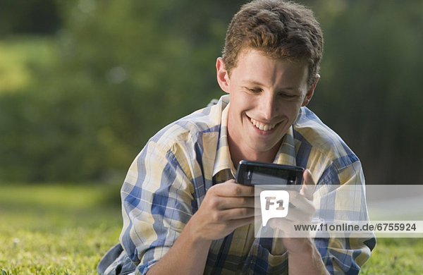 Man laying in grass and text messaging