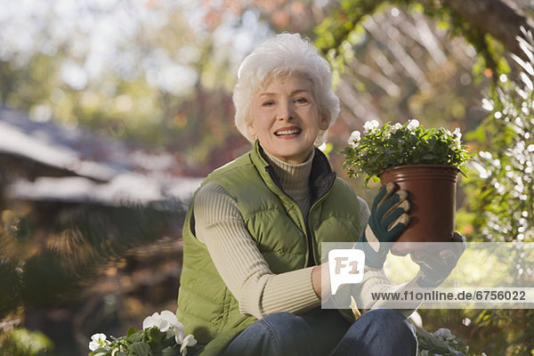 Senior woman sitting in domestic garden holding potted plant  portrait