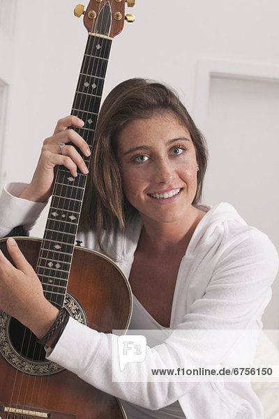 Junge Frau hält Gitarre