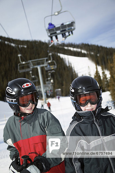 Skiers Standing Under Chair Lift  Alberta Rocky Mountains