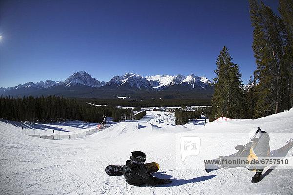 sitzend  Snowboard  hoch  oben  Gelände