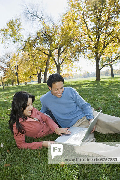 Couple looking at laptop in grass