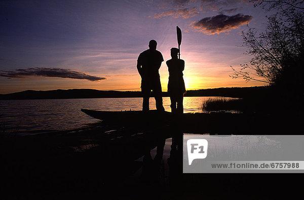 stehend  nebeneinander  neben  Seite an Seite  Sonnenuntergang  Silhouette  Kajak  Yukon