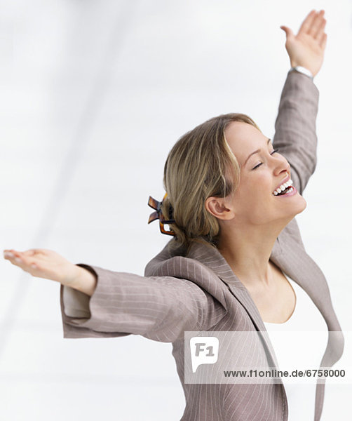 Happy businesswoman celebrating with arms outstretched