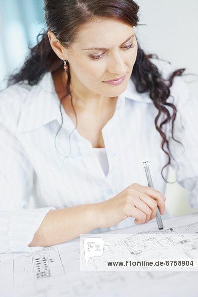 Woman looking at blueprints