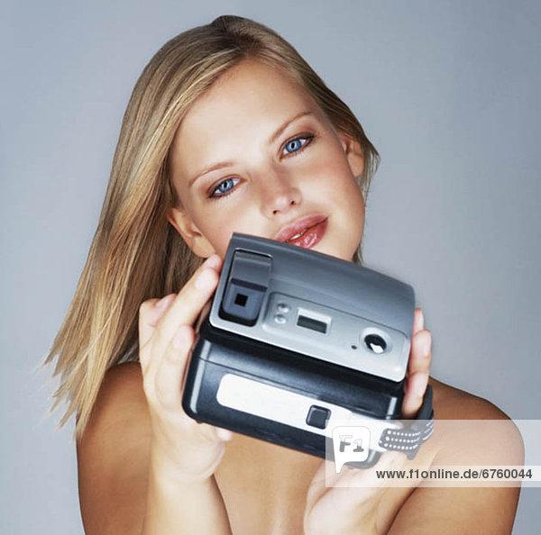 Nackte blonde Frau hält eine Kamera