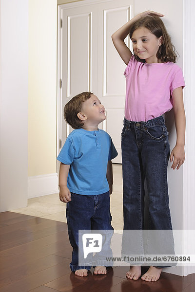 Brother Watching his Sister Measure her Height against a Door Frame  Toronto  Ontario