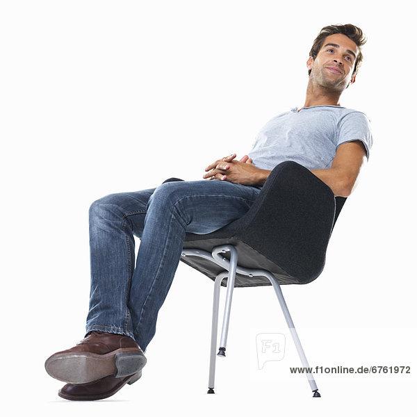 Studio shot of young man balancing on chair