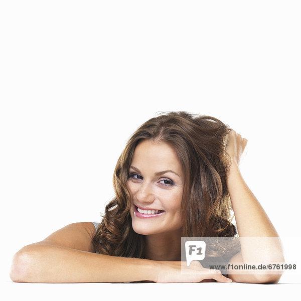 sitzend  Portrait  Frau  lächeln  jung  Studioaufnahme  Tisch