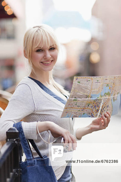 USA  Seattle  Smiling young woman holding map