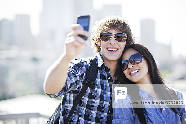 USA  Washington  Seattle  Couple wearing sunglasses photographing themselves with smart phone