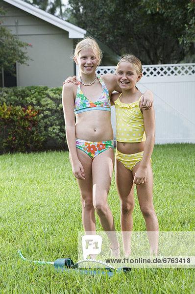 Girls playing with sprinkler in backyard