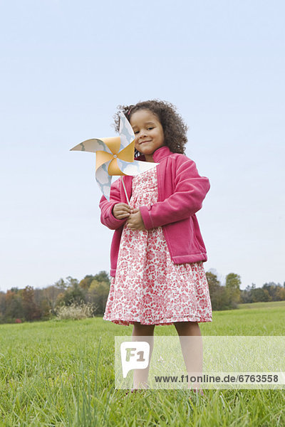 Girl playing with toy windmill
