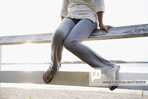 Legs of woman sitting on rail fence  lake in background