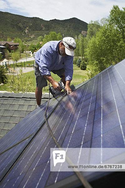 Dach bauen arbeiten installieren Sonnenkollektor Sonnenenergie Tisch