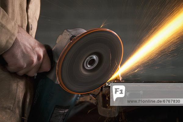 Steel grinder working in metal shop