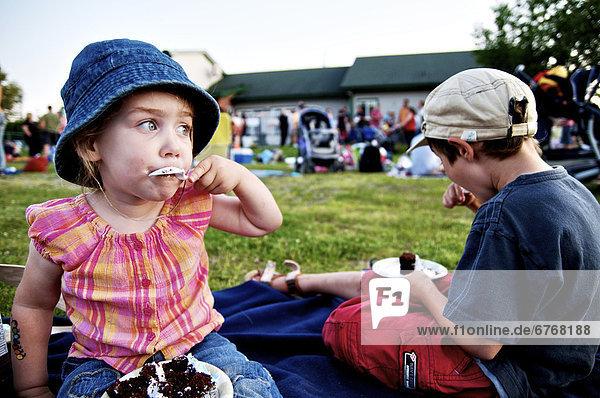 Young girl eating chocolate cake at an outdoor picnic  Otterburn Park  Quebec