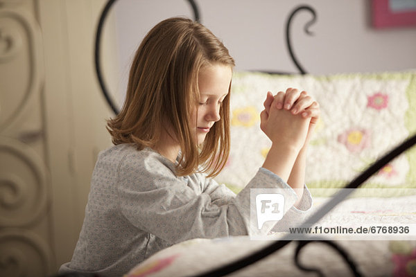 Young girl praying before bed