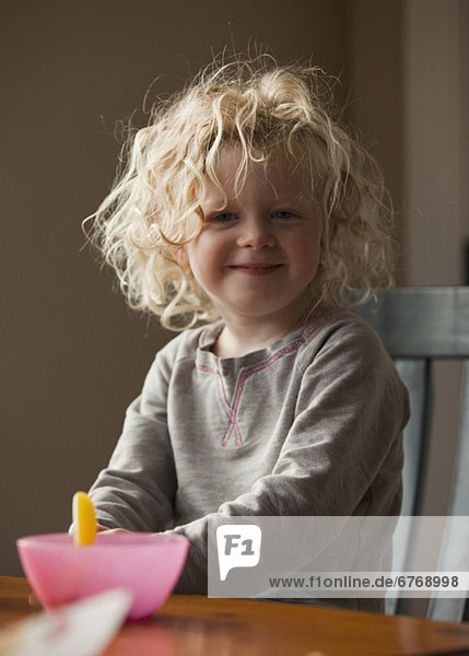 Young girl sitting at breakfast table