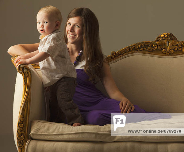Woman and toddler sitting on antique sofa