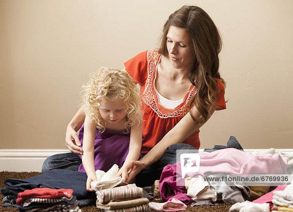 USA  Utah  Lehi  mother and daughter (2-3) folding laundry