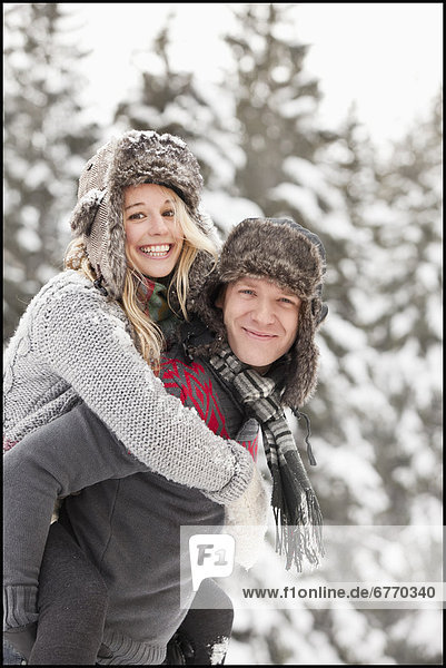 USA  Utah  Salt Lake City  man giving young woman piggy back ride in snow